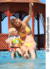 beautiful woman with blond little girl sitting on ledge pool open-air, woman shows forefinger upwards