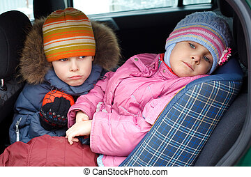 The sad boy with the little girl, in winter clothes in the...