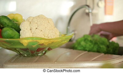 Housewife cleans a green salad in water. woman washing vegetables