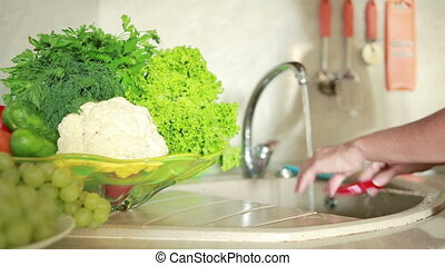 Female hands washing red chili at the kitchen sink. woman washes vegetables