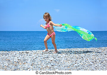 pretty little girl with fabric on stony seacoast