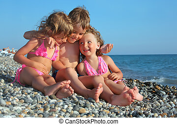 children three together sitting on stony beach