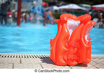 orange lifejacket near pool in aquapark