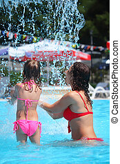 Smiling beautiful woman and little girl bathes in pool under water splashes, standing back