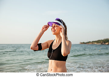 Runner girl wearing earphones and running armband ready for...