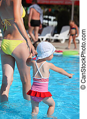 beautiful woman and little girl going on paddling pool in...