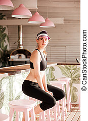 Young sports woman resting after workout at the beach cafe -...