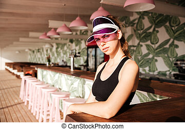 Sports woman resting after workout in a beach cafe - Young...