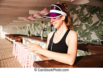 Sports woman listens music with earphones and smartphone in...