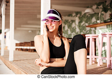 Young attractive sports woman talking on smartphone in cafe...