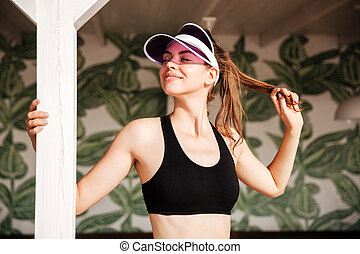 Smiling woman resting after workout on palm leaves pattern...