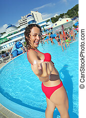Smiling beautiful woman standing in pool of an entertaining...