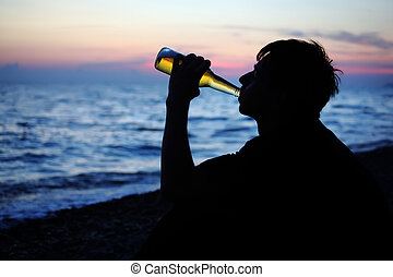 Silhouette teenager boy drinking beer on stone seacoast in...