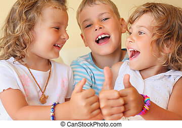Smiling children three together in cosy room shows ?? gesture