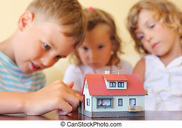 children three together looking at model of house standing on table in cosy room, focus on house