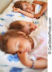 children three together sleeping on bed in cosy room, focus...