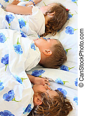 children three together sleeping on bed in cosy room