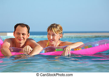 young man and nice women lying on an inflatable mattress in pool