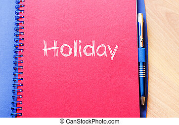 Holiday text concept on notebook - Holiday text concept...