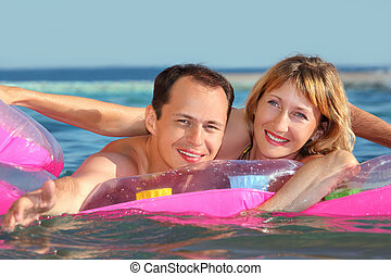 young man and nice women lying on an inflatable mattress in pool, man extended hand forward