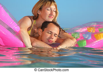 young man and nice women sleep on an inflatable mattress in pool, closed eyes