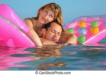 young man and nice women lying on an inflatable mattress in pool, man closed eyes