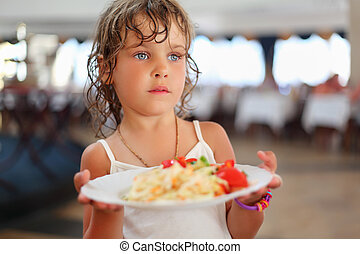 little pretty girl with dishes in hands at restaurant
