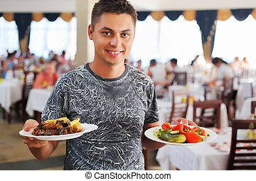 young smiling man with two dishes in hands at restaurant