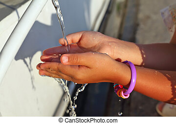 washing of hands of little girl by water from pipe in street...