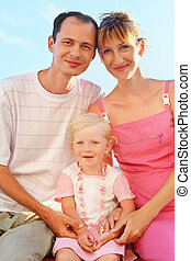 Happy family with little girl on beach, Parents hold  girl for hands