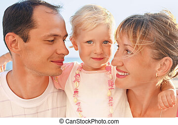 Happy family with little near to sea