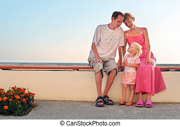Happy family with little sitting on bench on resort