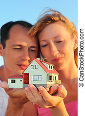 Young woman and man keeping in hands model of house