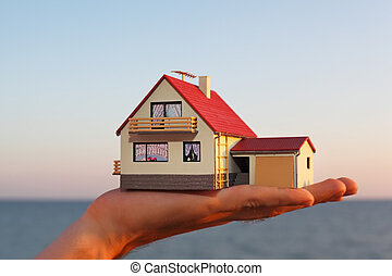 model of house with garage on hand against sea