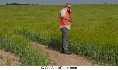 Farmer walking and talking on smart phone at cereals field