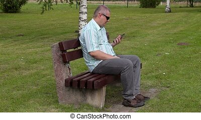 Stressful man with tablet PC in the park on bench