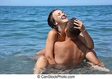 young hot woman sitting astride man in sea near coast,...