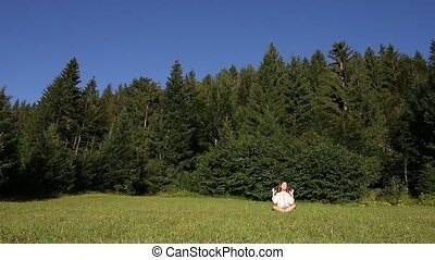 little girl meditating in front of the forest