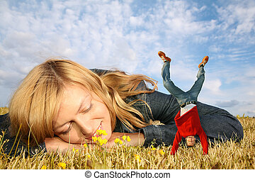young woman lies on the grass and miniature boy on hands...