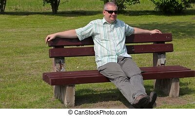 Tired man relax on bench in summer