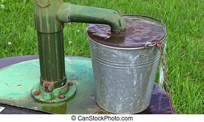 Water flowing over the edges of the bucket near water pump