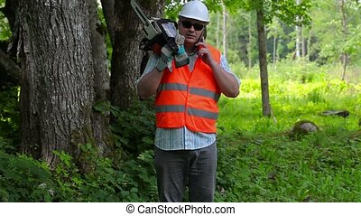 Lumberjack with cell phone and chainsaw near tree