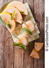 Honeydew melon juice closeup on wooden background, vertical...