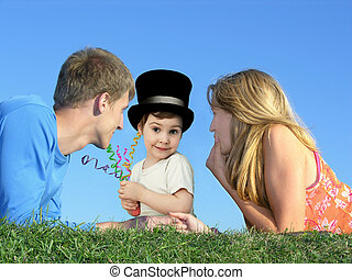 child in a hat with a mother and father on a grass, collage...