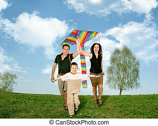 father, mother and child on grass with kite, collage