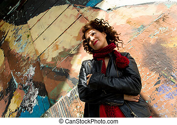 Young woman enjoying sun on the street with graffiti wall