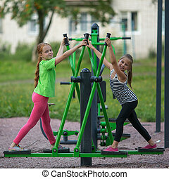Kids girls practice gymnastics on the public sport equipment...