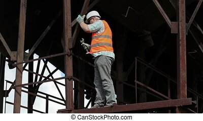 Worker using adjustable wrench near tanks