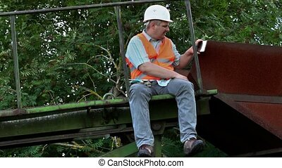 Worker sitting and take pictures on smart phone