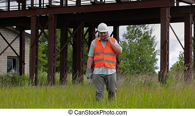 Worker with adjustable wrench walking and talking on cell...